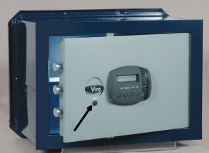 The arrow indicates the protective cap of the security lock which can be used to open the safe if the batteries run out.